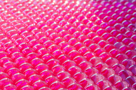large group of transparent hydrogel balls lined  in diagonal in fuchsia color