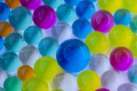 close up of multicolored hydrogel balls in different sizes, white background