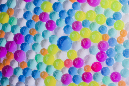 group of multicolored wet hydrogel balls on white background