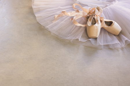 white tutu and pointe shoes on a grey concrete floor, copy space