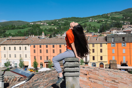 brunette with very long hair sitting on a chimney on the top of the roof in a village square on the hills Stock fotó