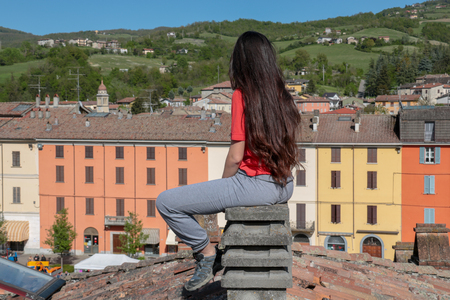 brunette in sportswear with very long hair sitting back on a chimney on the top of the roof in a village square on the hills