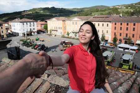 portrait of a country girl sitting on a roof top  of a building in a village square by the hand of a man