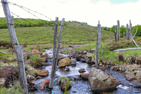 barbed wire on fence of wooden poles in the hills crossing stream Imagens - 124983011