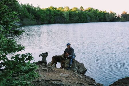 senior man with his border collie dog sitting on the shore of the lake
