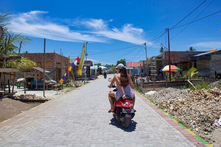 Kalimantan, Maratua island - August 30, 2018:  two european people ride the street of a village by  motorbike in island of Borneo