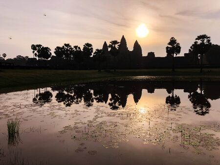 silhouette of Angkor Wat temple and its reflections in a pond, Siem Reap Cambodia at sunrise