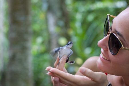 young woman smiling bringing newborn turtle in the fingers