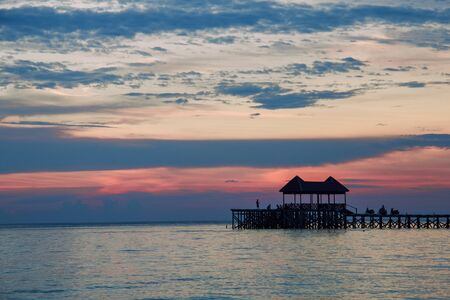 silhouettes of wooden pier and people at tropical sunset on the sea