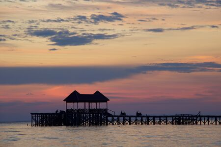 silhouette of wooden pier  in tropical island at amazing sunset