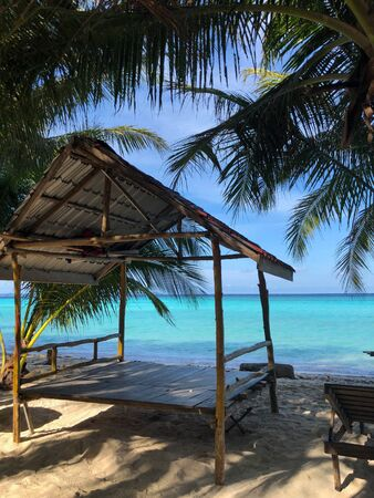 wooden hut on a tropical beach between palm trees in front of the turquoise sea