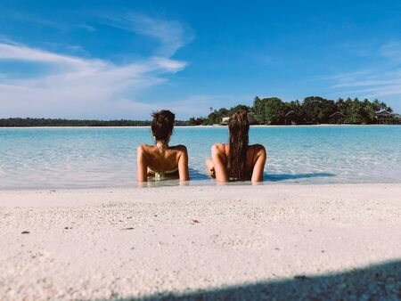 two young woman lying down on the water in exotic beach, Derawan island Stock Photo
