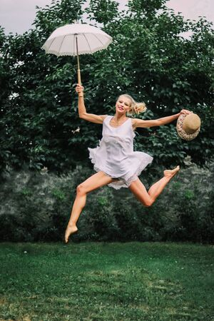 blond young woman jumping in a dance position with white parasol in the hand, green nature background