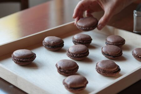 chocolate macarons arranged on a wooden tray, copy space