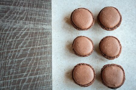 group of chocolate macarons on wooden  background, view from above