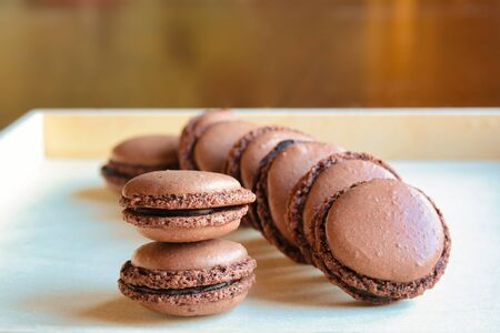 group of homemade chocolate macarons on a wooden tray