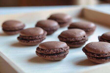 soft focus on chocolate macarons on light wood tray