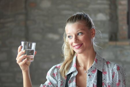 portrait of blond smiling woman looking  happy at a glass of water