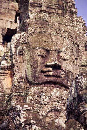 details of large carved face of buddha in Angkor Thom temple built in Bayon style, Cambodia