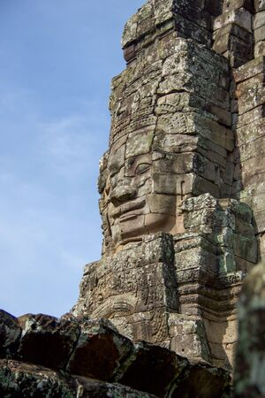 large buddha face carved  in a tower of angkor thom temple