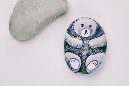 cute homemade painted stone  in the shape of bear on white background, copy space Stock Photo