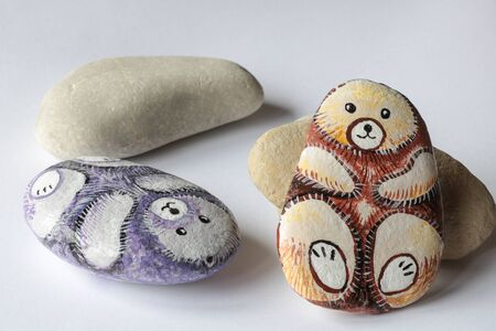 cute homemade painted stones as bears on a white paper background