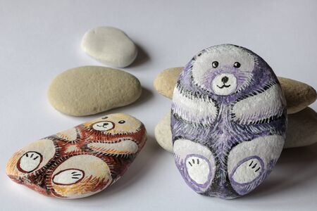 Two homemade painted stones in the shape of bears in different colors