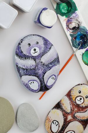 painted stones as bears view from above on white paper