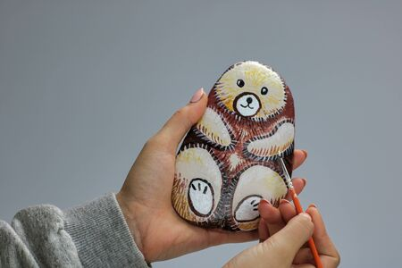 girl hands bringing and painting a stone as cute bear, gray background