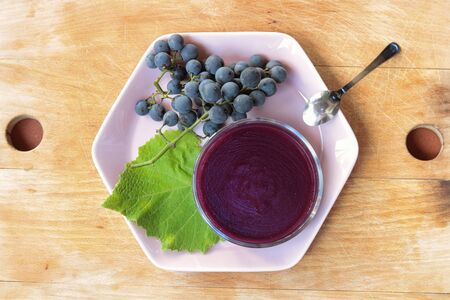 grape pudding  on a pink dish with a bunch of framboise grapes, wooden background