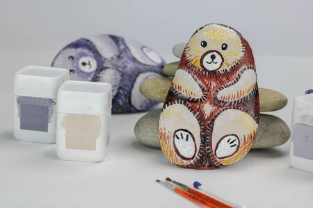 different colors for painted stones as bears on white paper Stock Photo