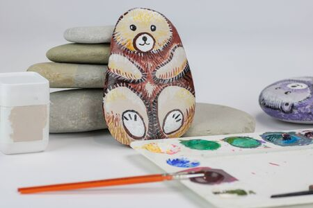 natural stones and handmade painted stones as bear on white background