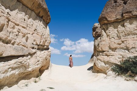young woman walking back between rocks in Goreme valley, Cappadocia Stock Photo