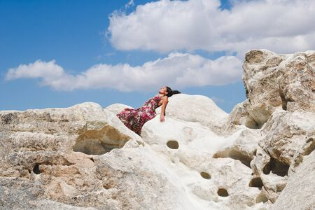 young beautiful brunette lying down on white rocks in a beautiful day of summer Stock Photo