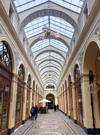 Paris, France - December 15, 2019:  some people visiting the beautiful Vivienne gallery in paris built in 1823 in neoclassic style with colorful mosaics on the ground