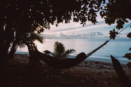 silhouette of person lying down on hammock in a tropical beach at down
