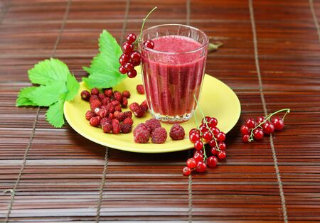 close up of red smoothie with red fruits on bamboo table runner