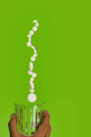 group of white pills suspended on drinking glass, green background, copy space Stock fotó - 154900778