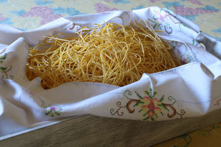 large group of dry egg spaghetti in wooden basket and embroidered fabric