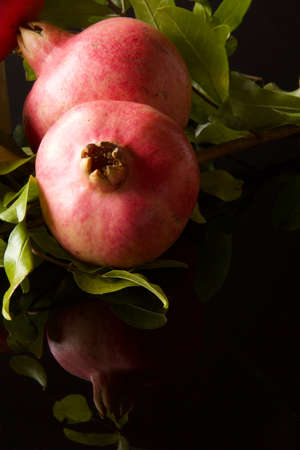 close up of pink pomegranate with green leaves reflected on black background Stock Photo