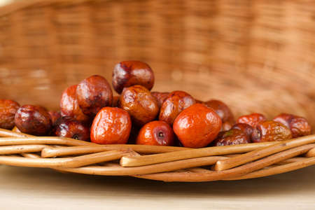 orange jujubes fruits in a wicker basket on a wooden table
