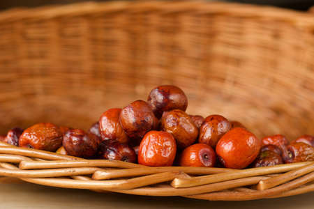 close up of dry orange jujubes fruits in a wicker basket