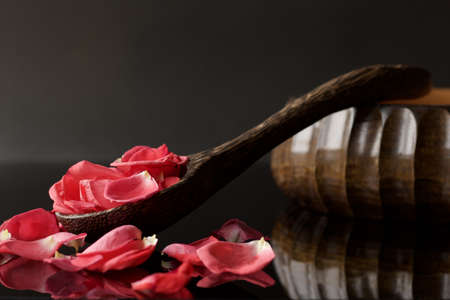 wooden ladle and oriental bowl full of rose petals on black reflected background Stock Photo