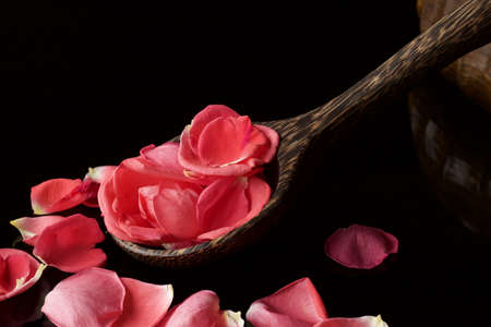 close up of wooden ladle full of soft rose petals on black reflected surface Stock Photo