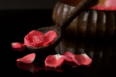 wooden ladle and bowl full of pink rose petals on reflected black background, concept of beauty
