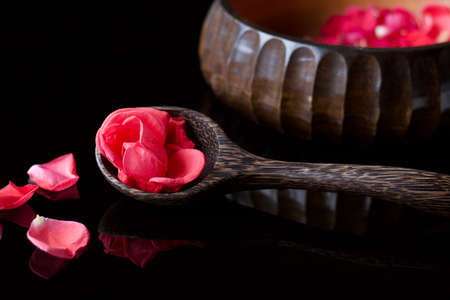 A ladle and bowl full of pink rose petals on black