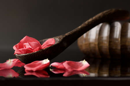 wooden ladle full of pink rose petals on black reflected background Stock Photo