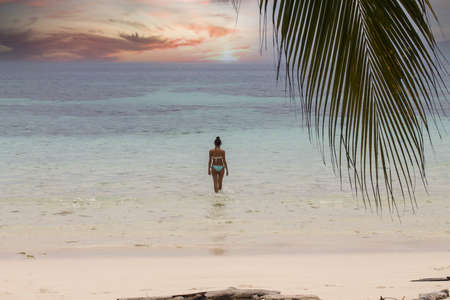 woman in bikini walking towards the sea on tropical beach at sunset Stock Photo