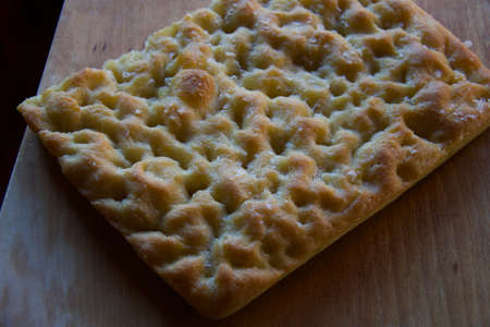 mediterranean italian focaccia freshly baked on wooden cutting board