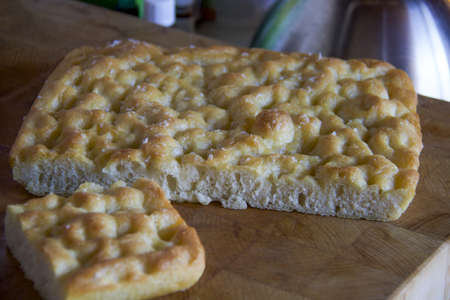 piece of homemade mediterranean italian focaccia on a wooden cutting board Stock Photo